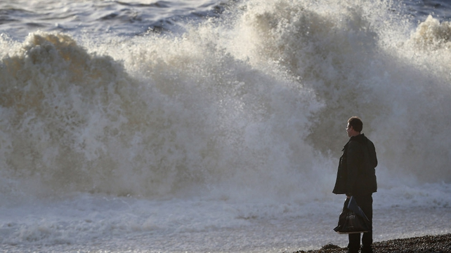 A man looks at waves during high tide on the seafront in Brighton