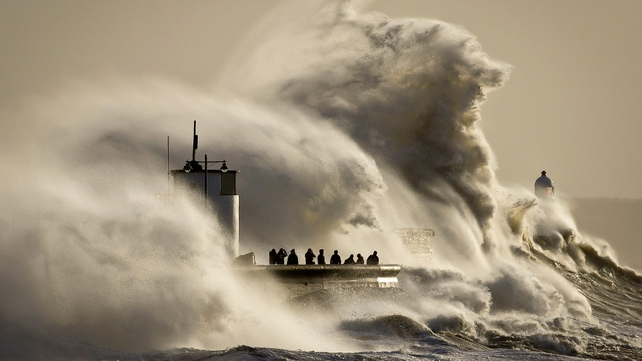 People watch and photograph enormous waves as they break on Porthcawl harbour, South Wales, where very strong winds and high seas created dangerous weather conditions