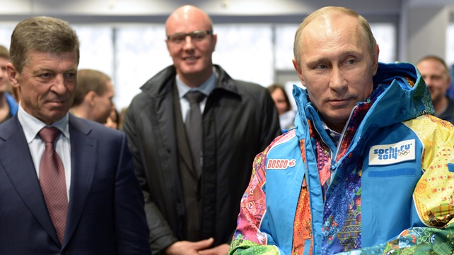 Russian President Vladimir Putin (R) tries an Olympic volunteers uniform, visiting an equipment centre in Sochi
