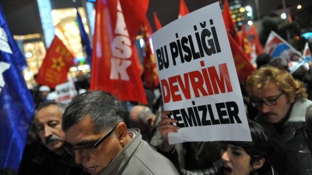 A Turkish protester holds up a placard reading 'Only revolution can clear this corruption' during a demonstration against the government