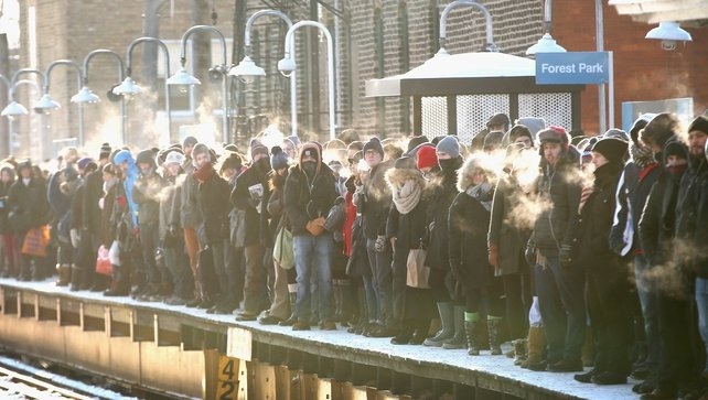 Passengers heading into downtown Chicago wait in sub-zero temperatures for the train to arrive