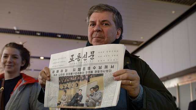 A man shows a North Korean newspaper as he arrives at Beijing's international airport from North Korea