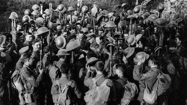 Men of the First Battalion of Irish Guards hold aloft their helmets as they hear the news of the Armistice