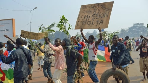 Demonstrators holding a placard reading 'Djotodia Resign' march to Mpoko airport