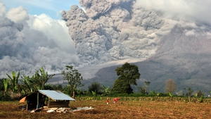 Indonesian villagers work on their field as Mount Sinabung spews volcanic materials