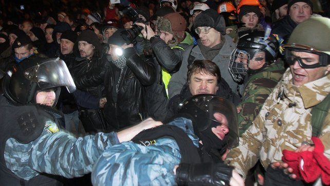 Ukrainian pro-European opposition activists clash with riot police after a rally near a district court in Kiev