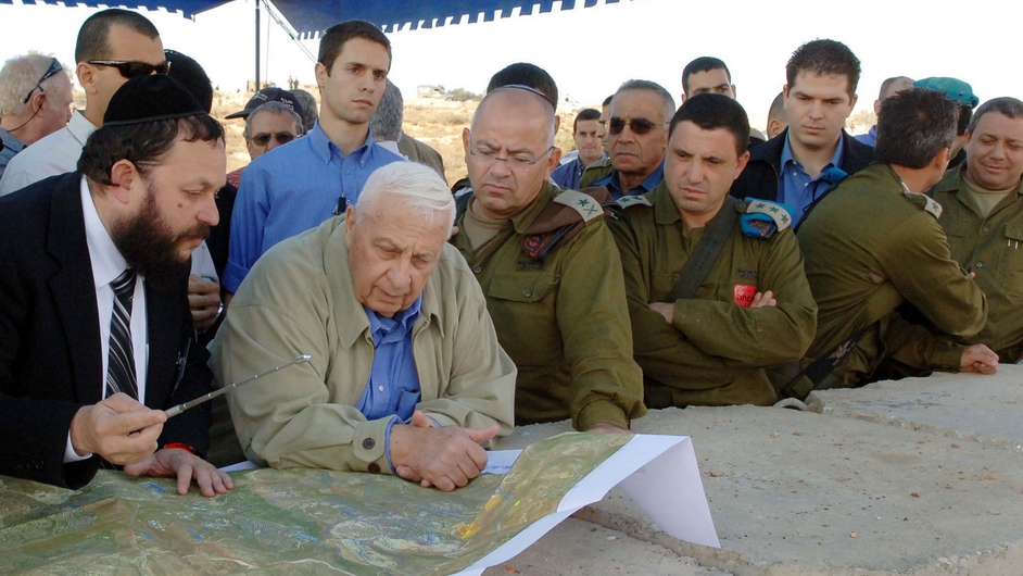 Mr Sharon is briefed by Yaakov Guterman on the route of Israel's separation barrier in Modi'in Illit in 2005