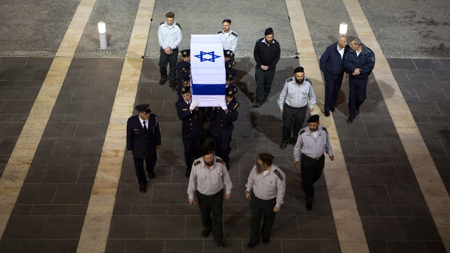 Israeli honour guards carry the coffin into the Knesset