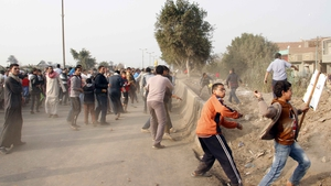 Egyptian Muslim Brotherhood supporters throw stones at voters outside a polling station