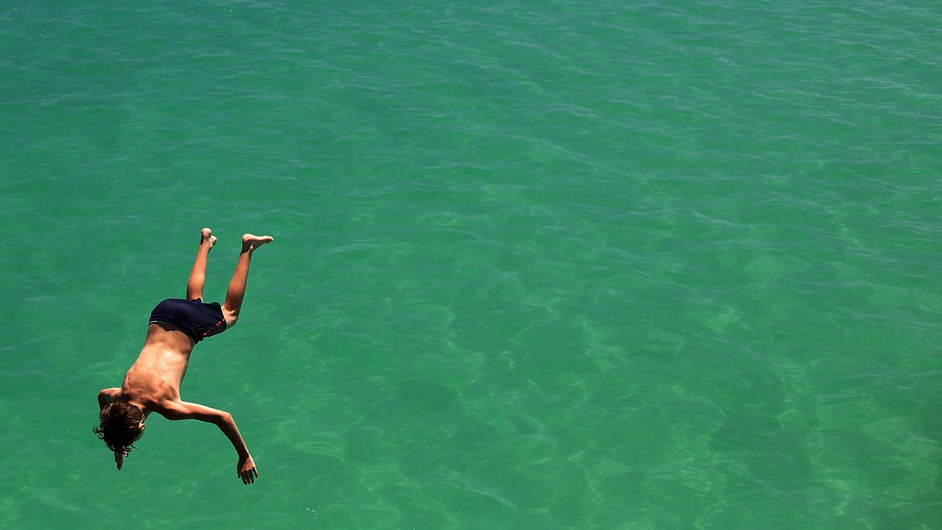 A man jumps from the jetty during the heat wave in Adelaide, Australia