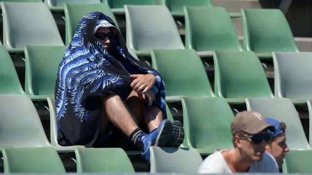 A fan covers himself from the heat with a towel at the Australian open