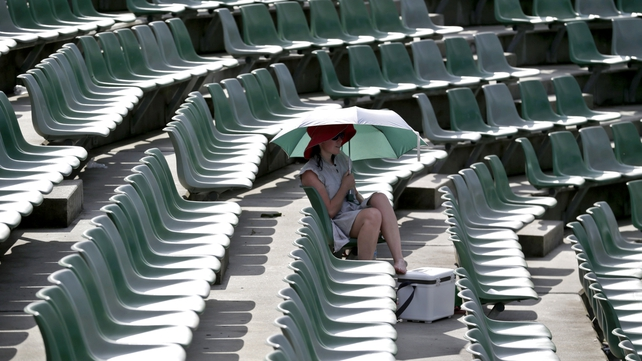 A single tennis fan sits under an umbrella as matches are suspended due to a heatwave