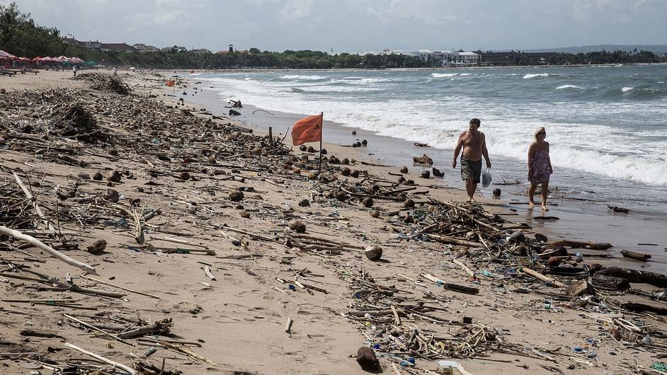 Tourists stroll along the trash-strewn beach