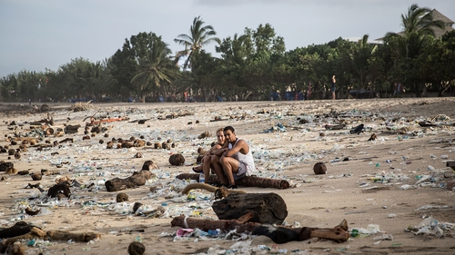Tourists sit among the waste