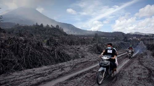 Motorcyclists passing through an area covered by ash following a series of eruptions of Mount Sinabung in Indonesia