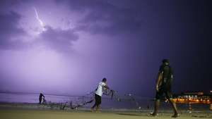 Fishermen gather their net along Copacabana Beach as lightning flashes during a powerful early evening thunderstorm