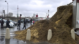 French police officers gather around a pile of manure which was dumped from a truck, in front of the French National Assembly