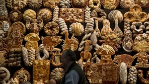 A visitor walks past a stand featuring various types of bread in the Russia Hall of the Gruene Woche International Agriculture Fair in Berlin