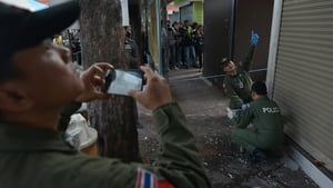 The Thai bomb squad unit examine the site of a blast at Victory monument in Bangkok