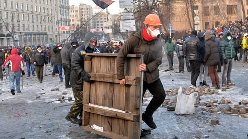 Protesters carry a wooden board to build barricades during clashes with the police in Kiev
