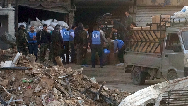 UNRWA staff members unload food packages at the besieged Yarmuk Palestinian refugee camp near Damascus