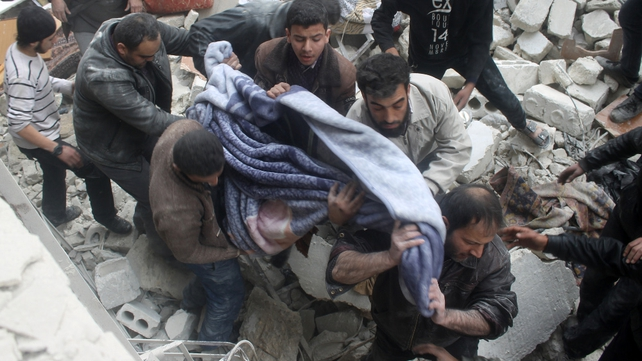The body of a victim killed in an air raid on Aleppo is pulled from the rubble of a collapsed building
