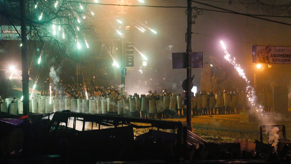 Protesters fire fireworks to a police line
