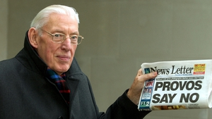 Mr Paisley smiles as he holds up a newspaper on 8 December 2004. His party refused to share power with Sinn Féin if there was no photographic proof the IRA had surrendered its complete arsenal