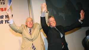 Mr Paisley holds up his hands with Peter Robinson as he arrives for his farewell speech at Balmoral Hall in Belfast on 30 May 2008