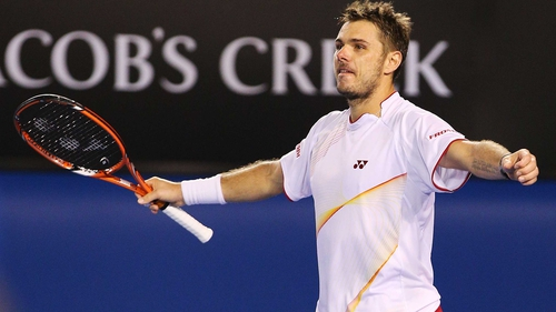 Stanislas Wawrinka raises his arms in triumph after Novak Djokovic volleys wide on match point