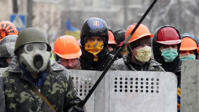 Protesters protect themselves from tear gas during an anti-government protest in Kiev