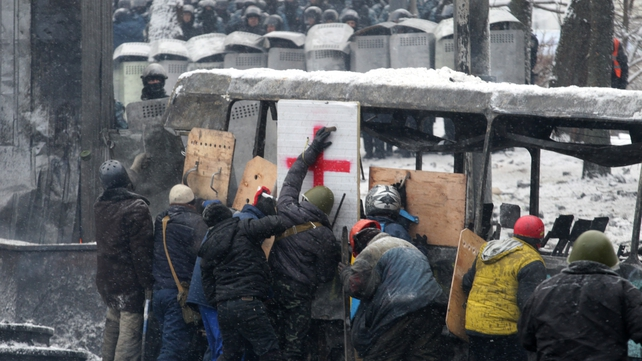 Protesters use a bus a shield in the centre of Kiev