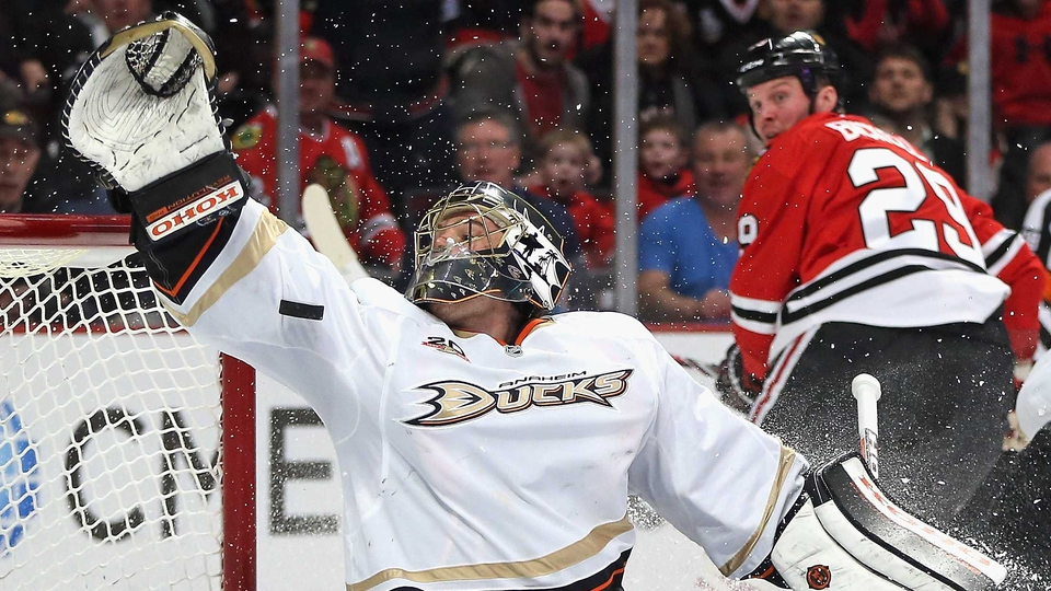 Jonas Hiller of the Anaheim Ducks tries to make a save on a goal shot by Bryan Bickell of the Chicago Blackhawks in Chicago