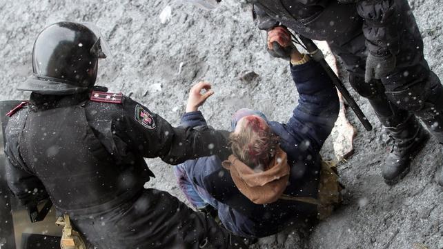 Ukrainian riot policemen detain a protester following clashes in central Kiev