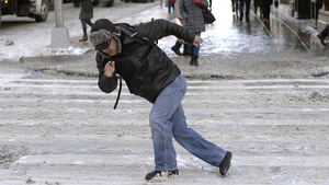 A man struggles to keep his feet on an icy 5th Avenue