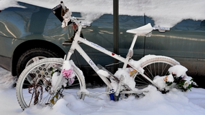 A bicycle decorated with flowers and messages, covered with snow on Fifth Avenue in NYC