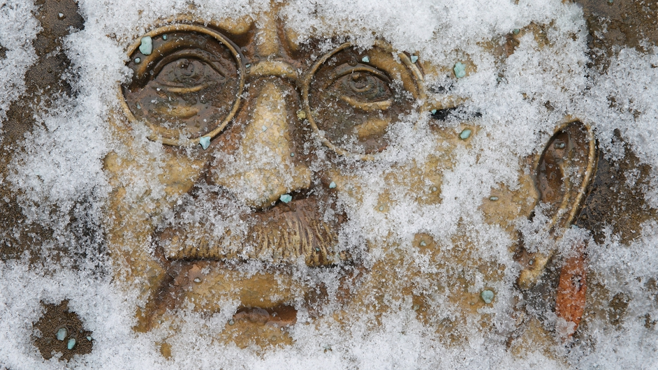 Snow obscures a relief sculpture of Gandhi near the White House