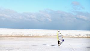 A man uses a sail to ski on Montrose Beach along the shore of Lake Michigan