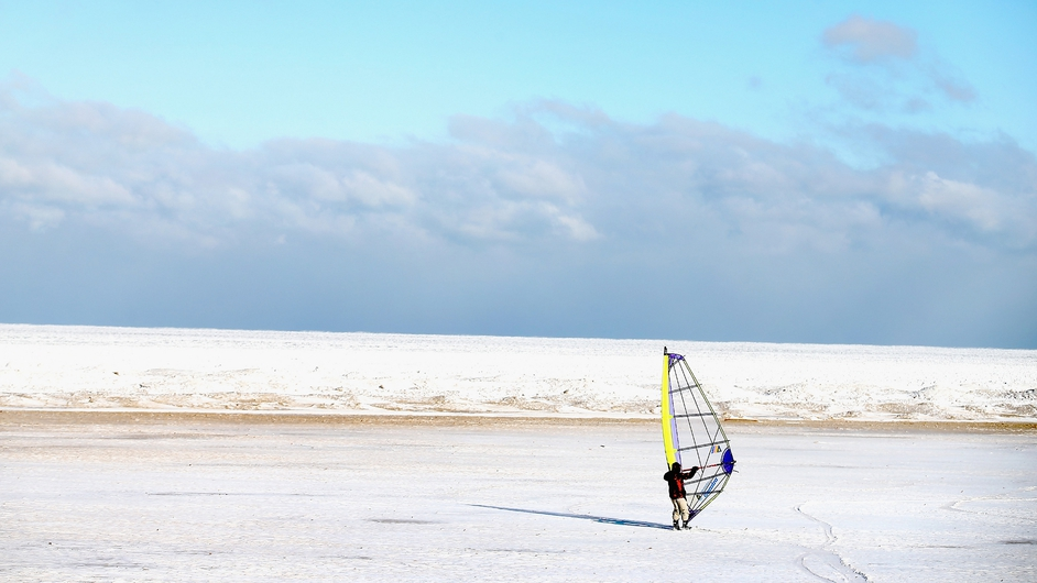 A man uses a sail to ski on Montrose Beach along the shore of Lake Michigan