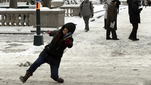 A woman falls on the ice and snow along 5th Avenue in New York