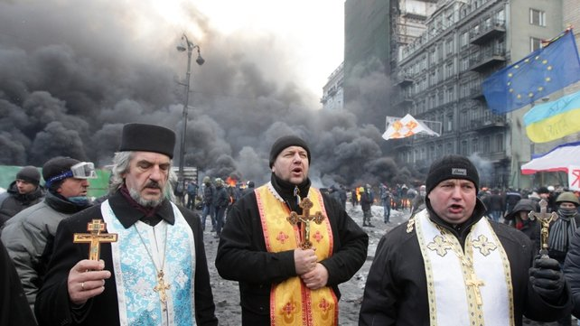 Orthodox priests pray during the protests (Pic: EPA)