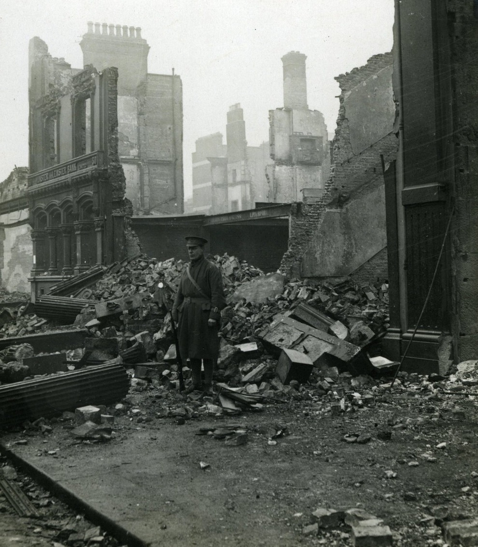 """A soldier on duty outside a ruined building"" held by UCD Archives. Digital image: © University College Dublin, published by UCD Digital Library. DOI: http://dx.doi.org/10.7925/drs1.ucdlib_30688"