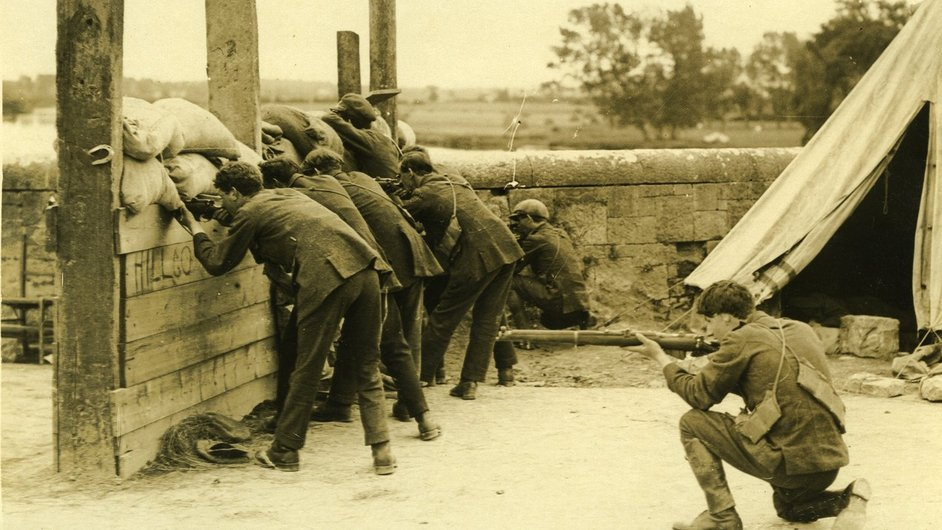 """Irish Free State Army soldiers crouched in defensive position at a barricade on a country bridge"" held by UCD Archives © WD Hogan. Digital image: © University College Dublin, published by UCD Digital Library. DOI: http://dx.doi.org/10.7925/drs1.ucdlib_30"