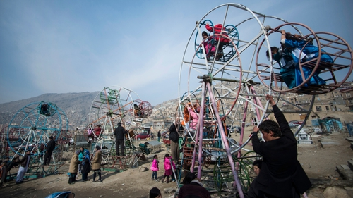 Afghan children ride on ferris wheels near a cemetery in Kabul