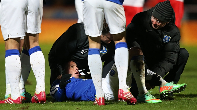 Everton's Bryan Oviedo lies injured after a tackle by Stevenage's Simon Heslop, resulting in a broken leg