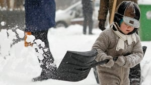 A young boy shovels snow in Bucharest