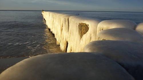 Groynes are coated in ice at the Baltic Sea beach in Ahrenshoop, Germany