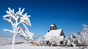 A church in the snow-covered winter landscape in Zinnwald-Georgenfeld, Germany