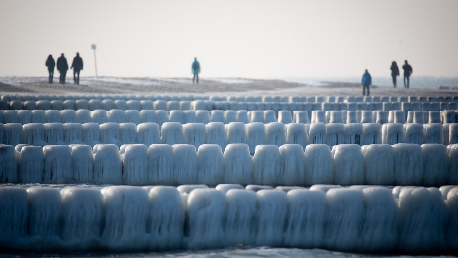 Strollers pass by the icy groynes at the beach in Ahrenshoop, as temperatures dropped below -10C