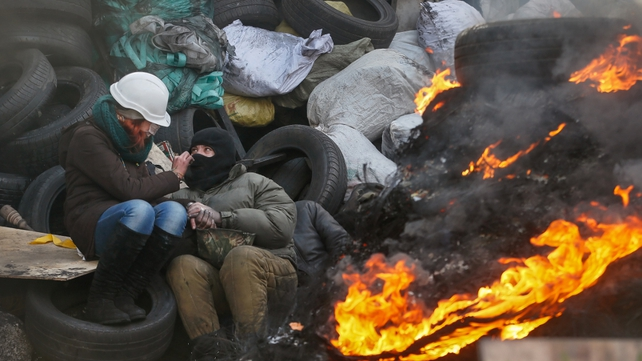 A couple warms themselves near a fire at a barricade in Kiev (Pic: EPA)